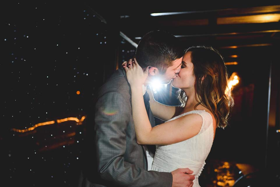 Bride and groom kissing outside in the rain at the Barn at the Springs Wedding Venue