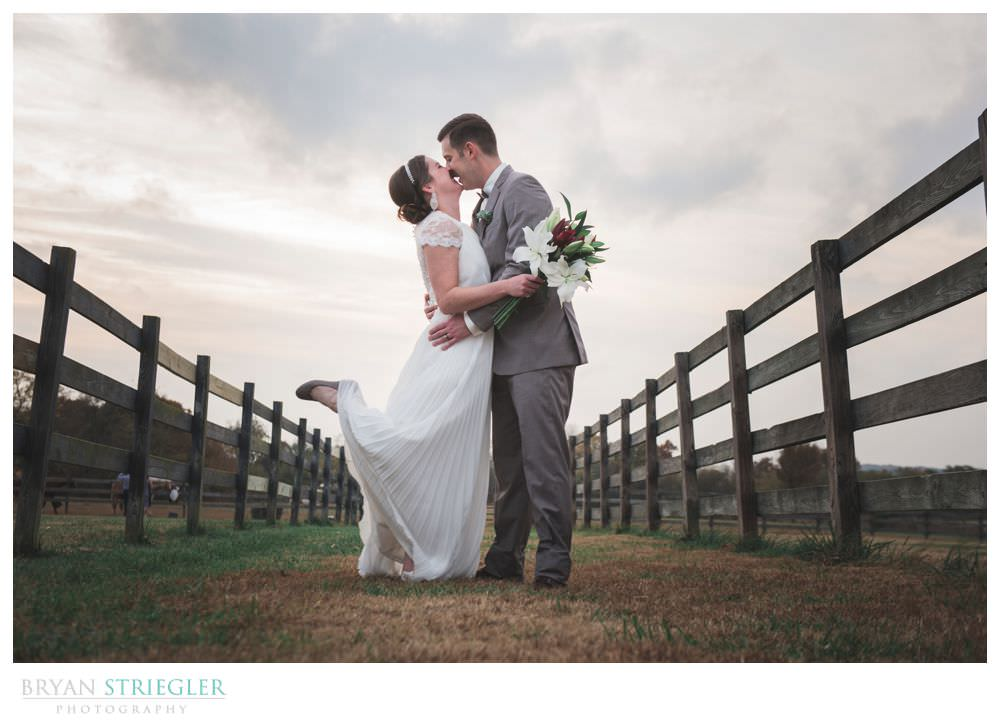 bride and groom with wood fences