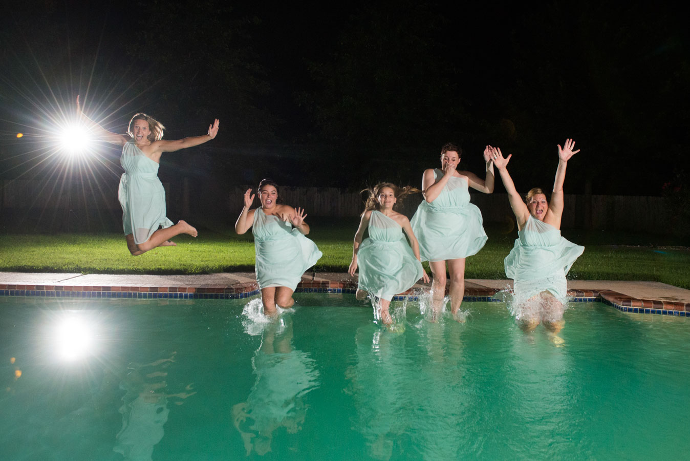 Bridesmaids jumping into the pool