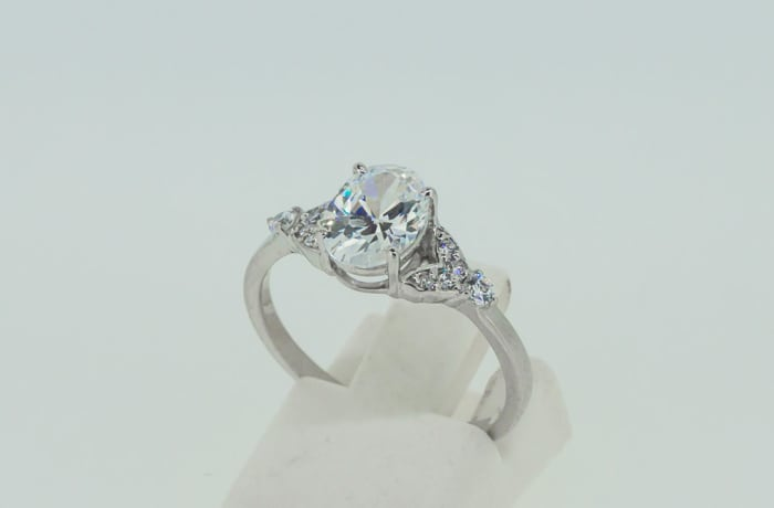Engagement silver four pronged solitaire crystal ring with heart accents