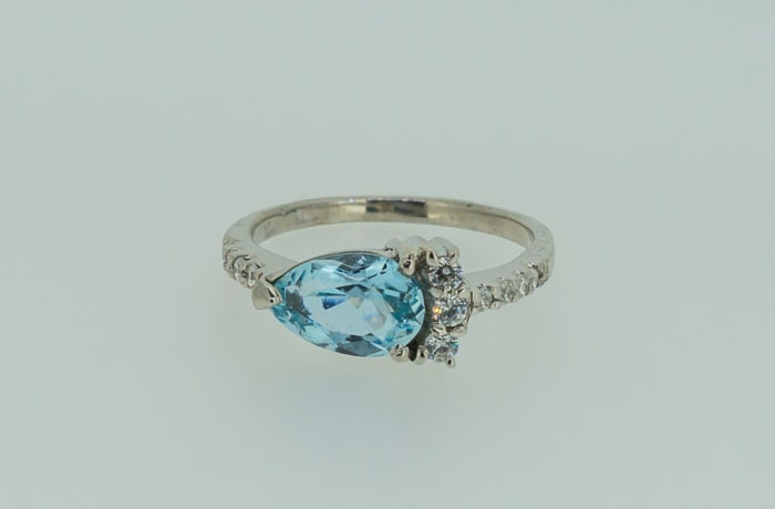 White gold pear cut sapphire engagement ring with set crystals