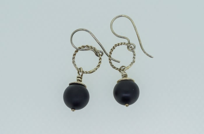 Silver earrings with black onyx gemstones on twisted rings