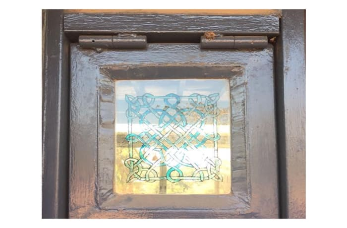 Glass pane in frame with an old  symmetric pattern image
