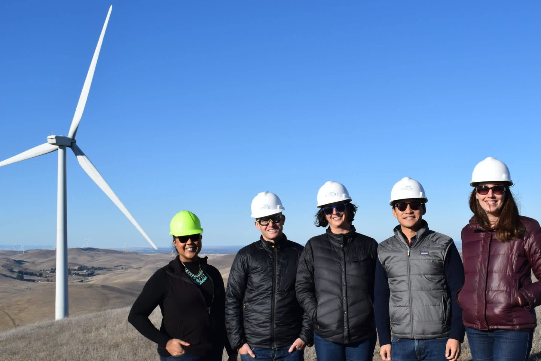 EBCE employees posing in front of an Altamont Pass turbine
