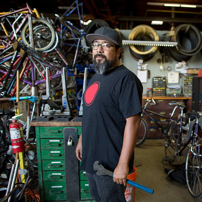 Man standing in his bike repair shop, looking at the camera, with lots of bikes and equipment around him