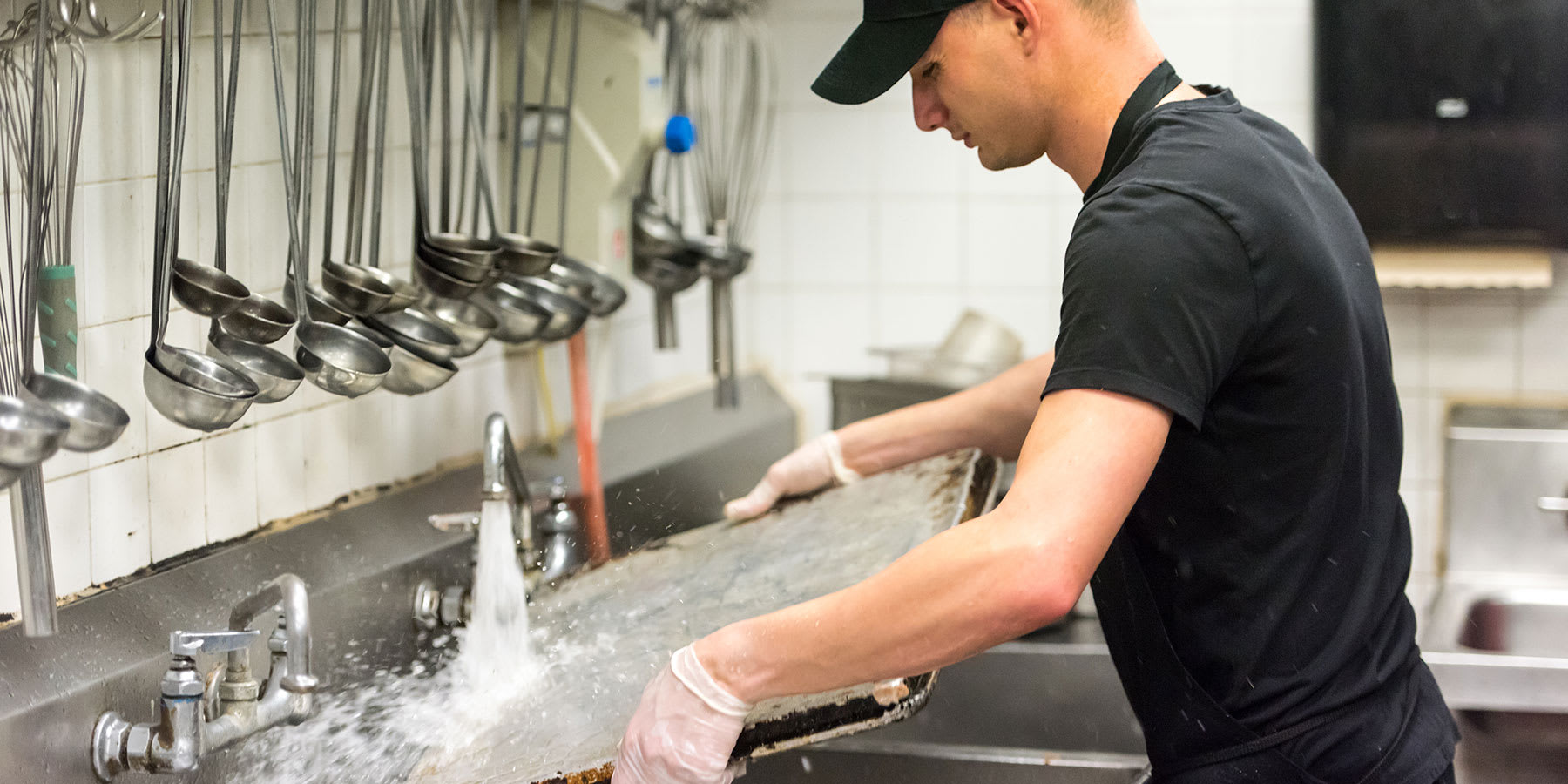Man washing large baking sheet in the sink of a commercial kitchen.