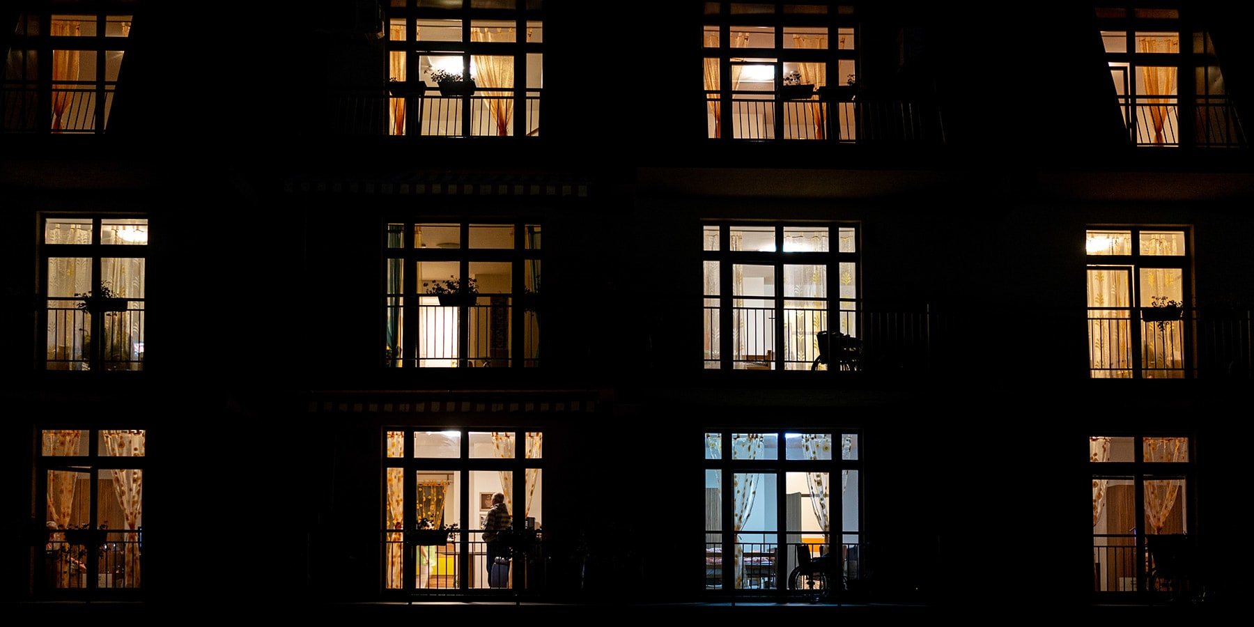 Grid of apartment building windows at night with light glowing from inside the homes.