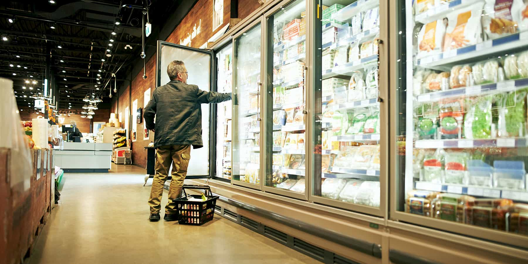 Man shopping in grocery story frozen aisle taking picking something out of the freezer shelf