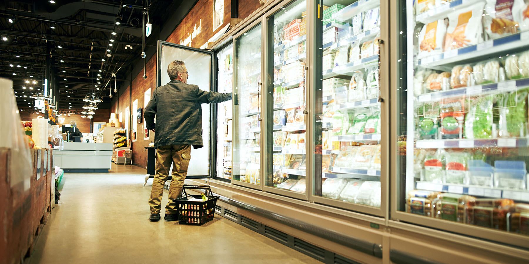 Man in grocery store freezer aisle opening freezer door to take product.