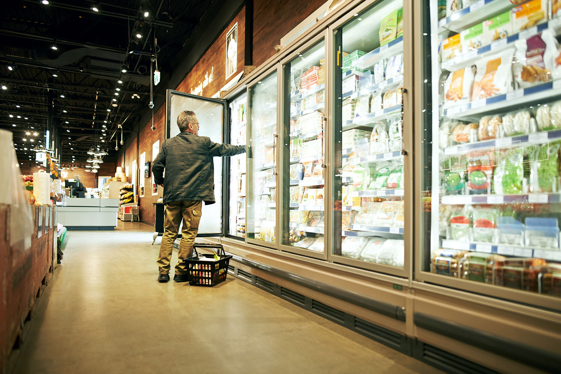 Man shopping in grocery store froze aisle and taking a product from the shelves.
