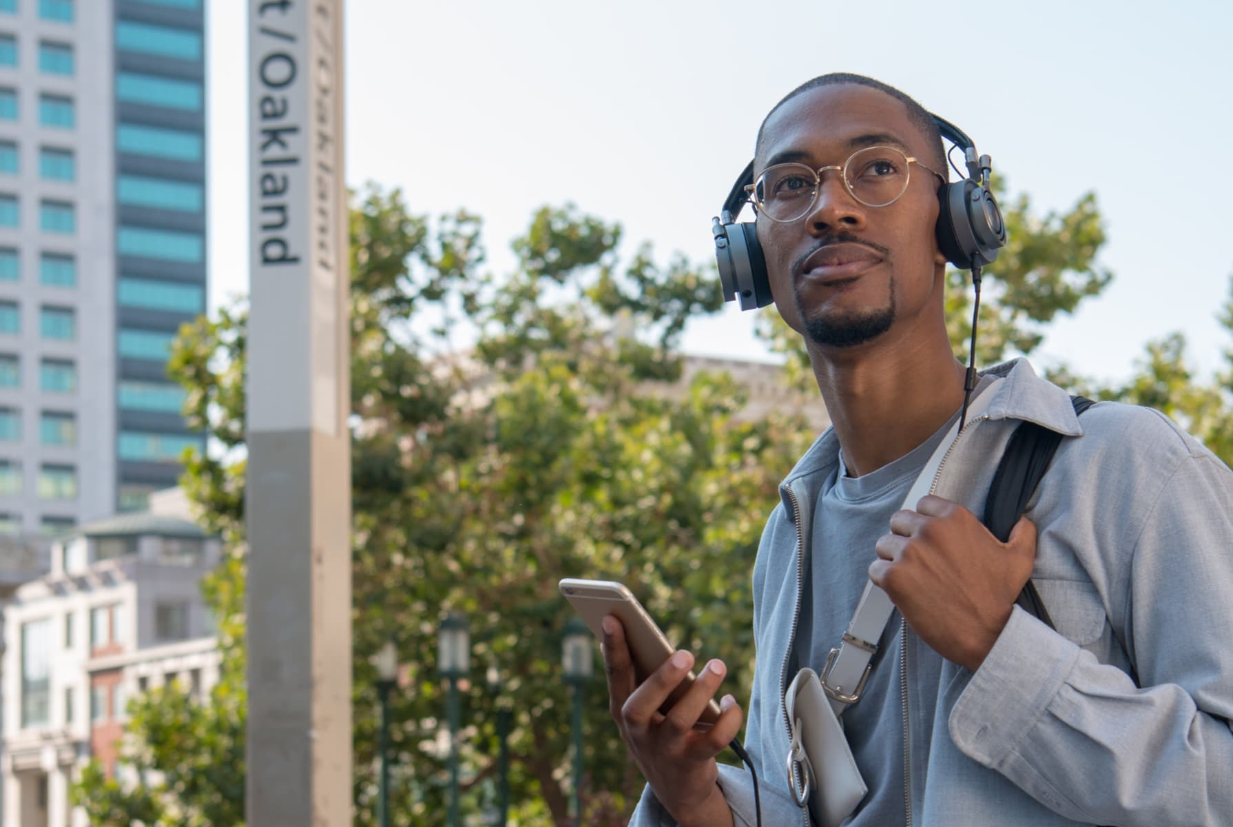 Man with headphones on standing on an Oakland city street.