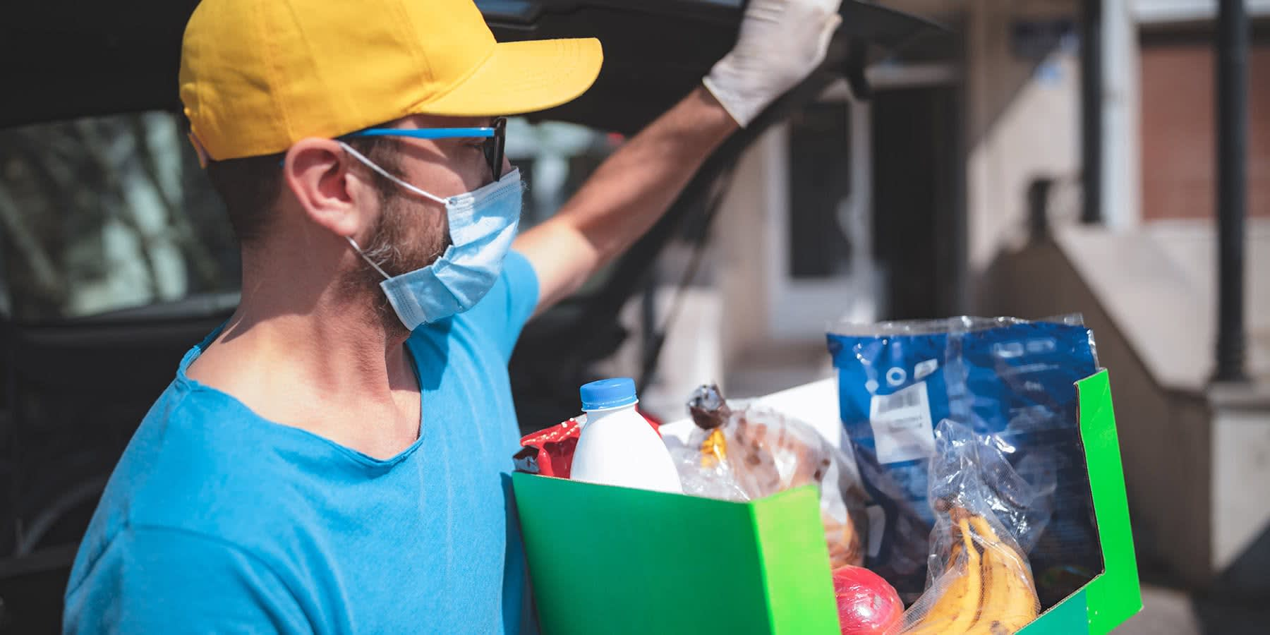 Man delivering a package of food with a mask and gloves on for social distancing