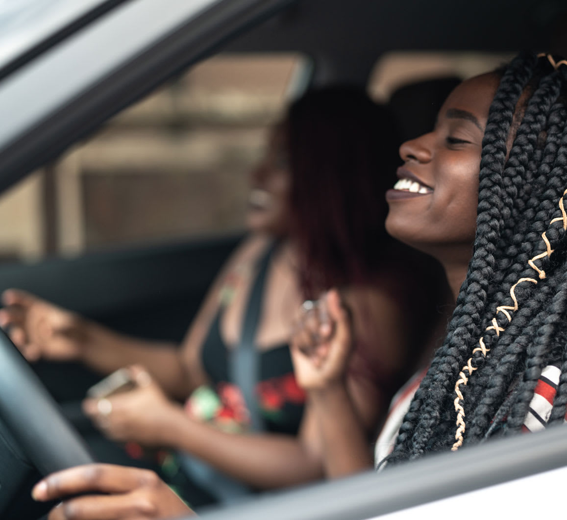 Smiling woman and friend in electric car