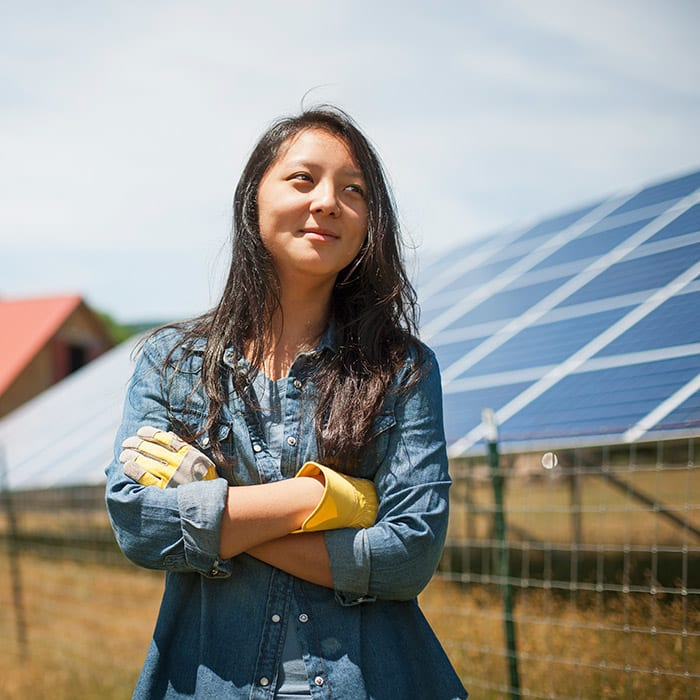 Woman standing proudly in front of solar panels with their work clothes on.