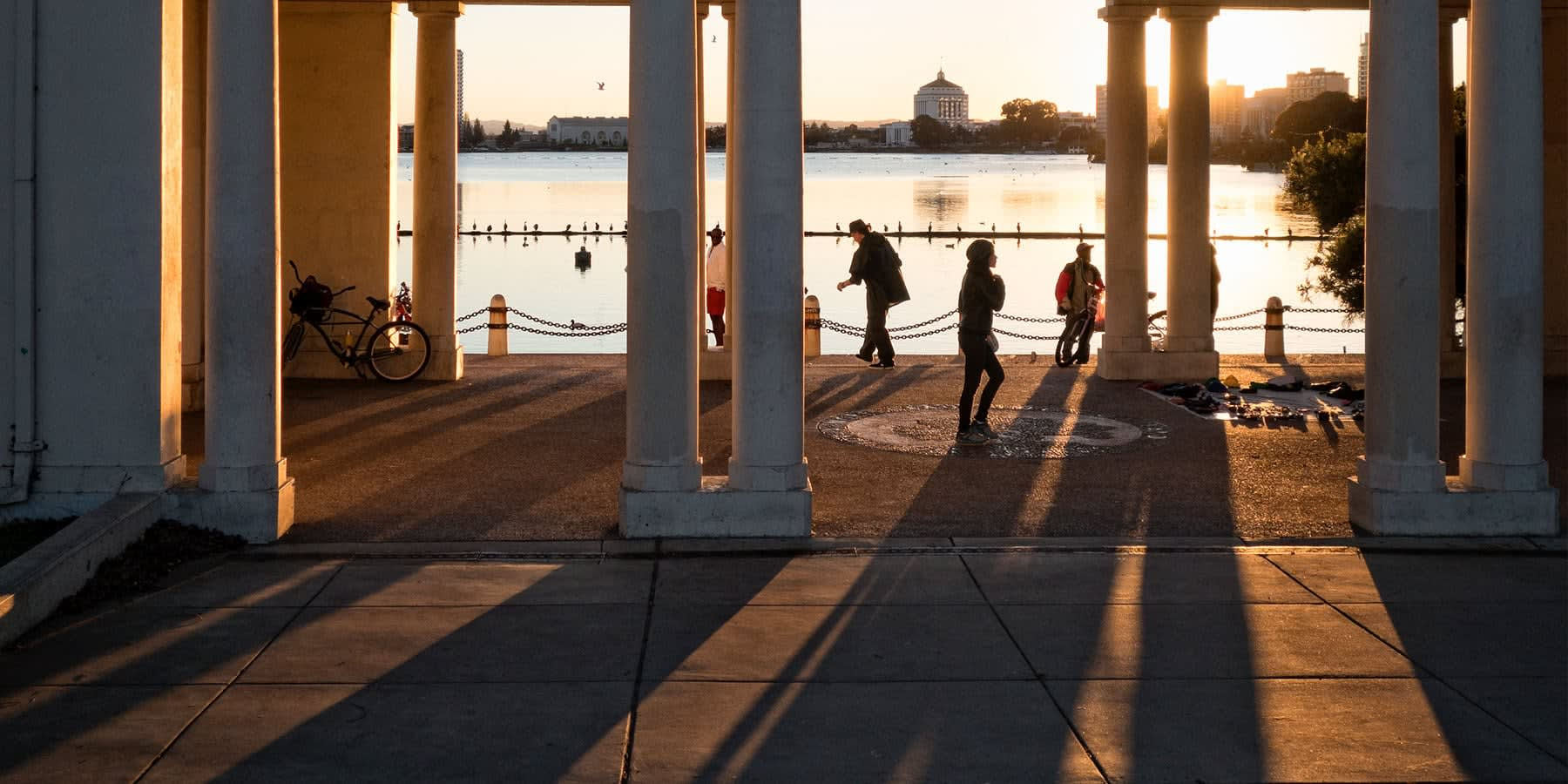 View of people walking under pillars by a lake in the sunset