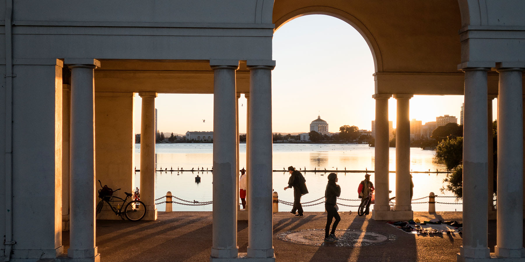 People walking through arch next to Lake Merritt at sunset