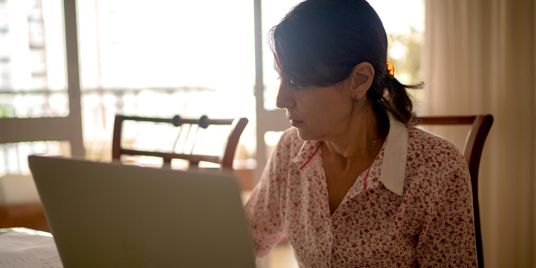 Woman sitting at her kitchen table in front of a laptop and some notes