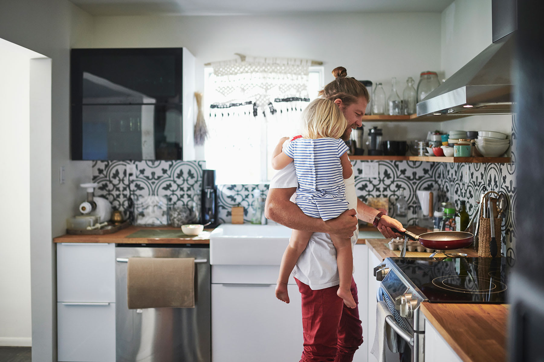 Father holding his daughter in the kitchen while cooking on an induction stovetop.