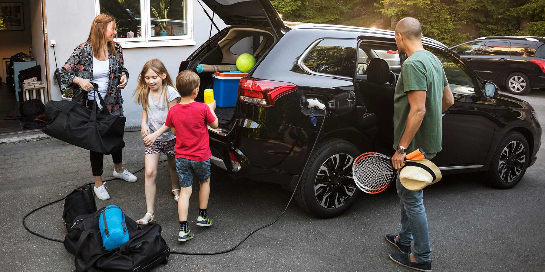 Family loading up an electric car.