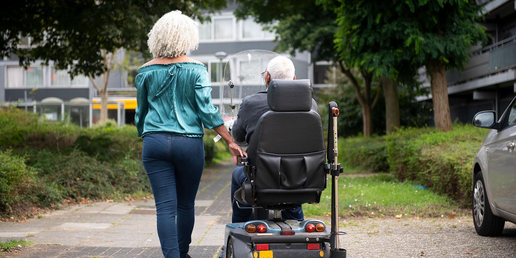 Elder woman walking next to her husband in a motorized wheelchair.