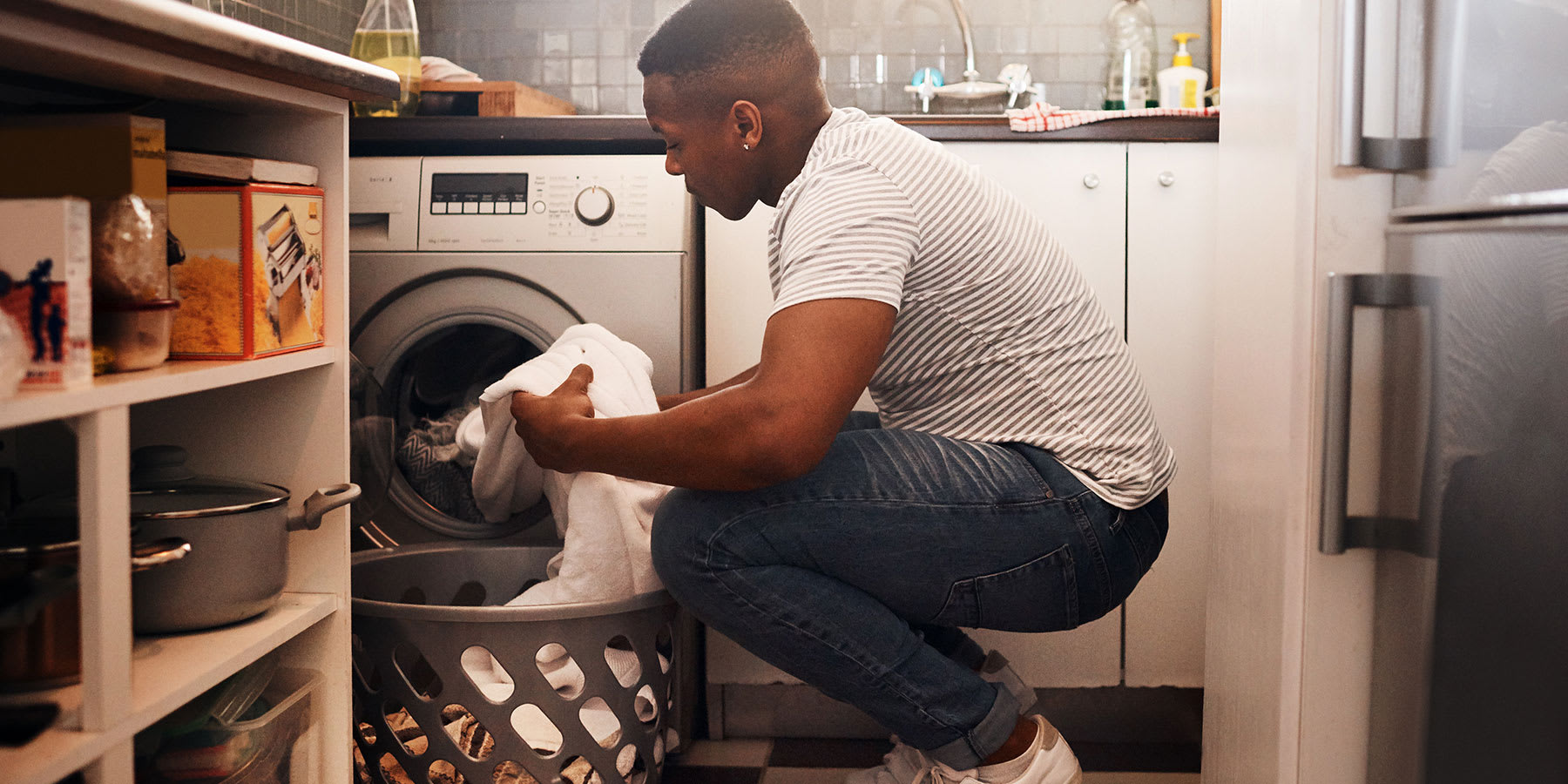 Man in his mid-20s loading the washing machine in his apartment