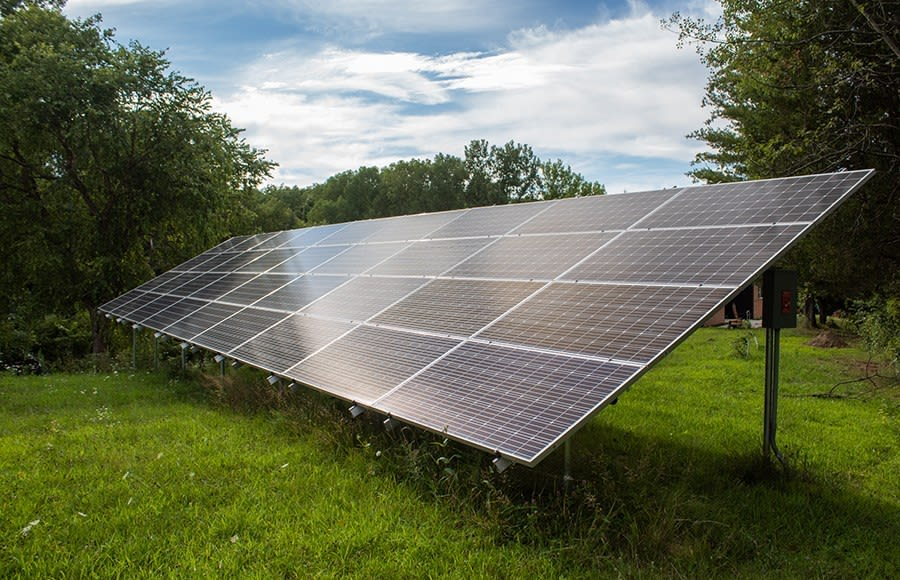 Solar panels in a grassy field surrounded by trees