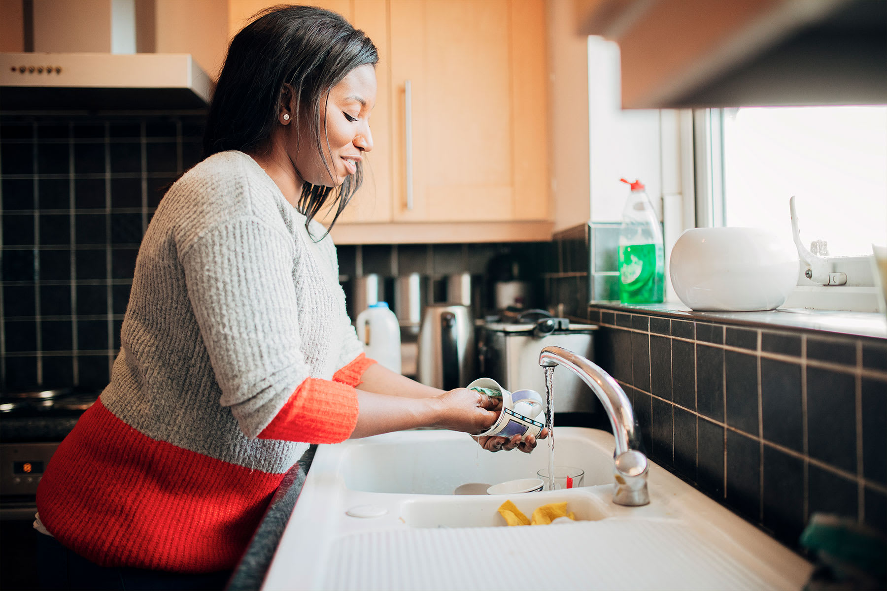 Woman washing dishes in her kitchen sink.