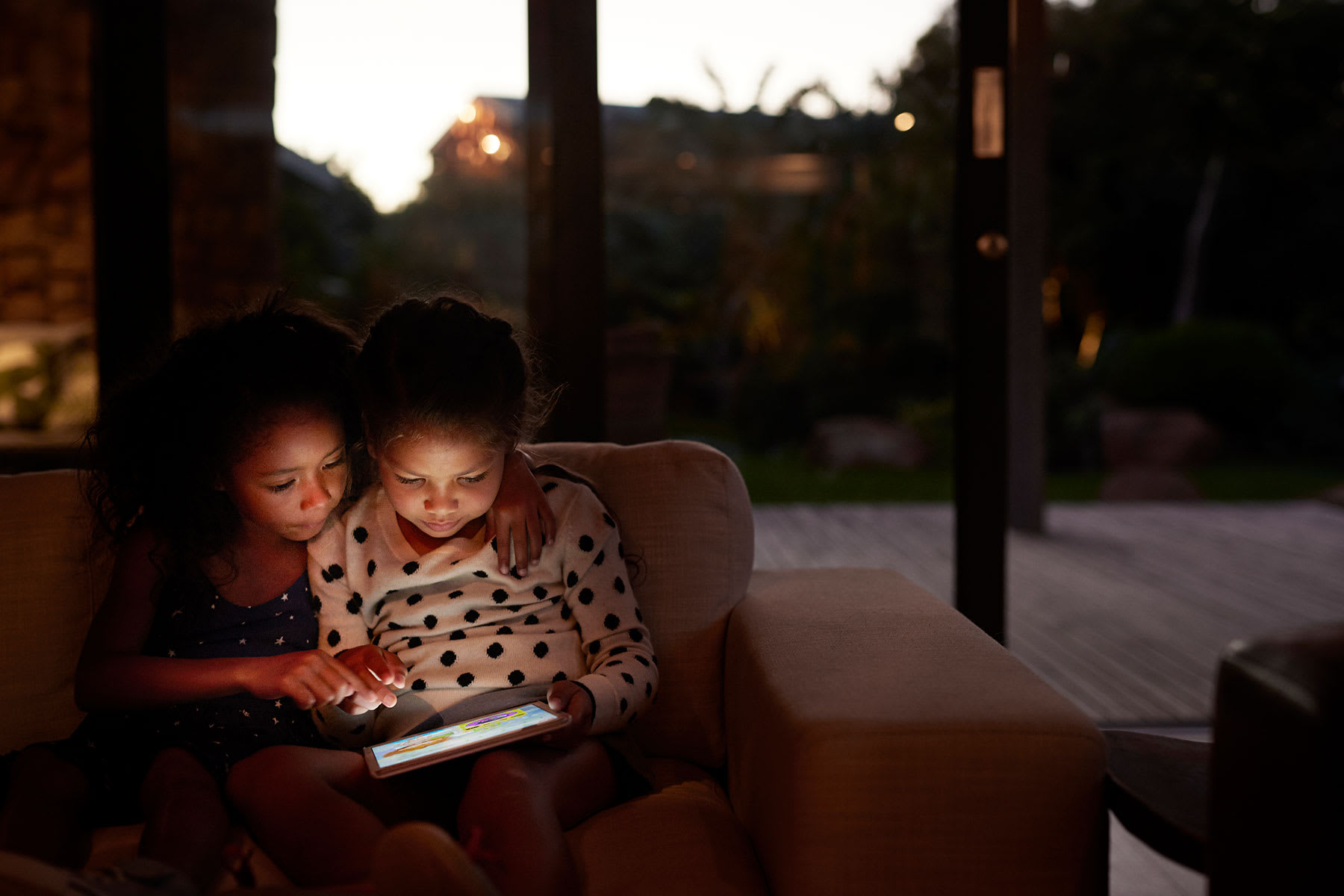 Two young girls using an electric tablet at home in a dark room.