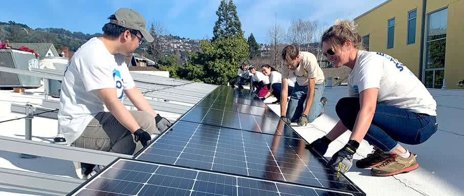 Grant recipients installing solar panels on a roof top