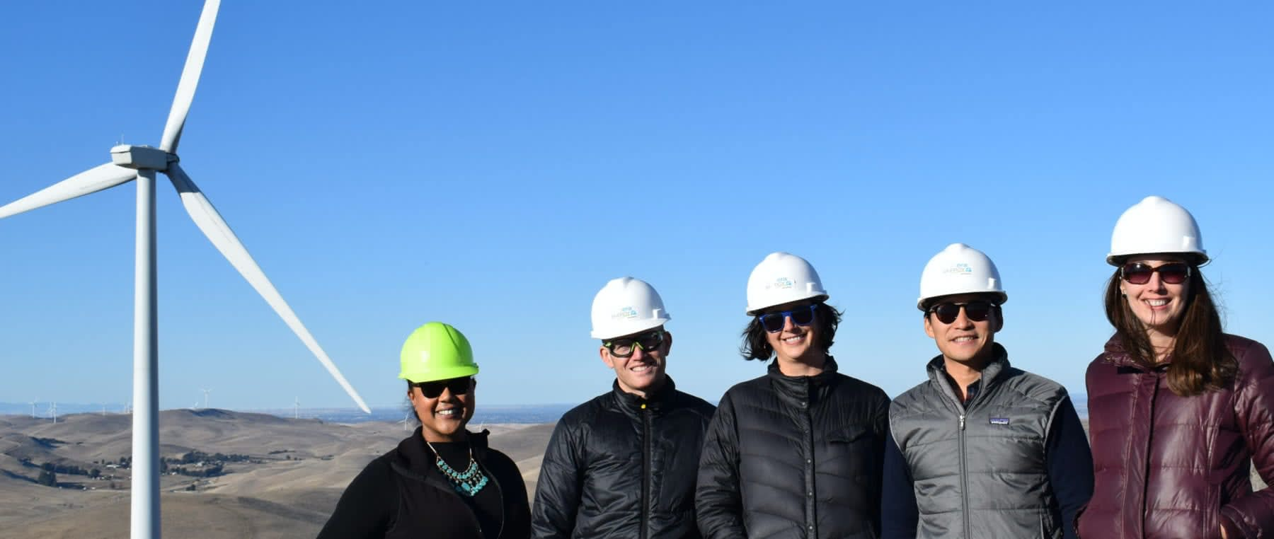 Five employees from the the EBCE team posing in front of a wind turbine with hard hats and sunglasses on.