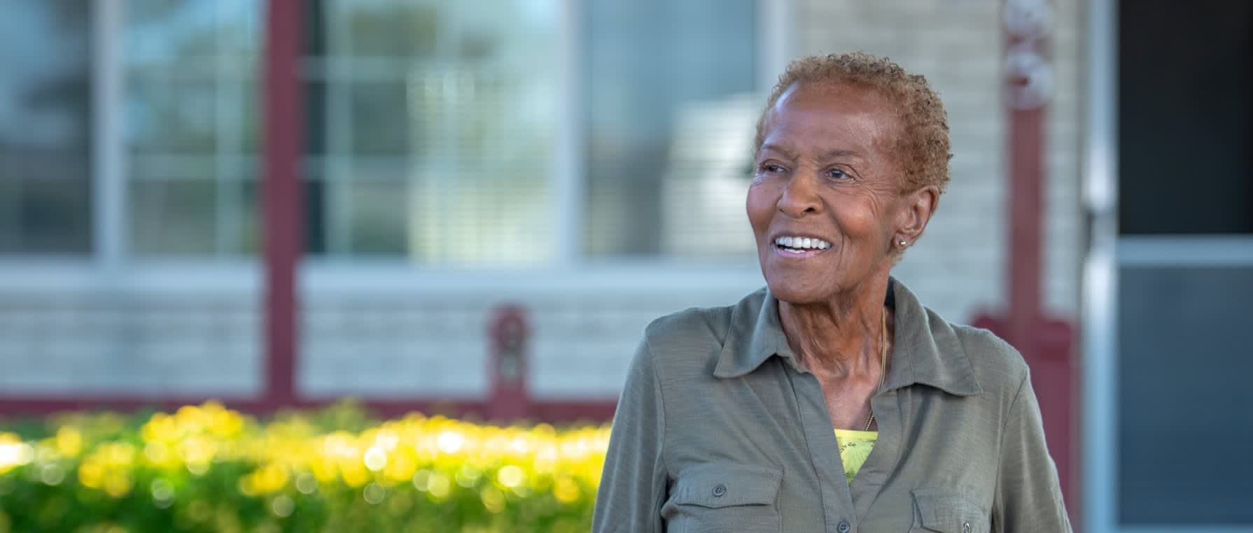 Picture of an African American elderly woman outside her home smiling.