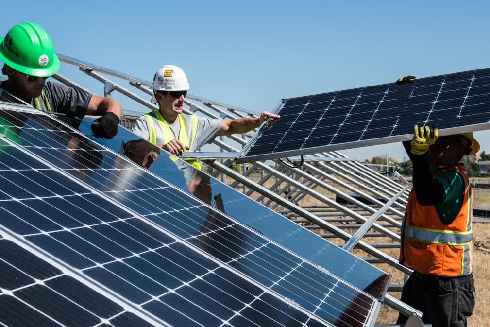 Three workers installing solar panels in a field