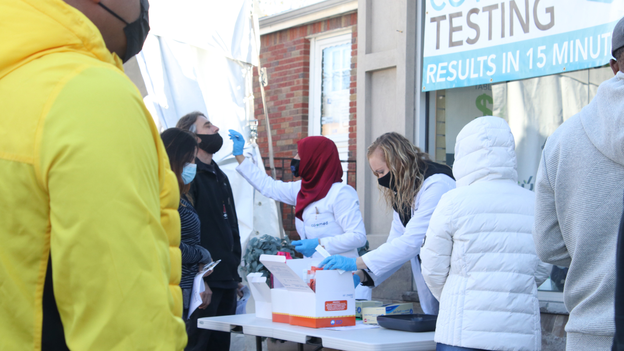 People getting COVID tests at an outdoor testing station