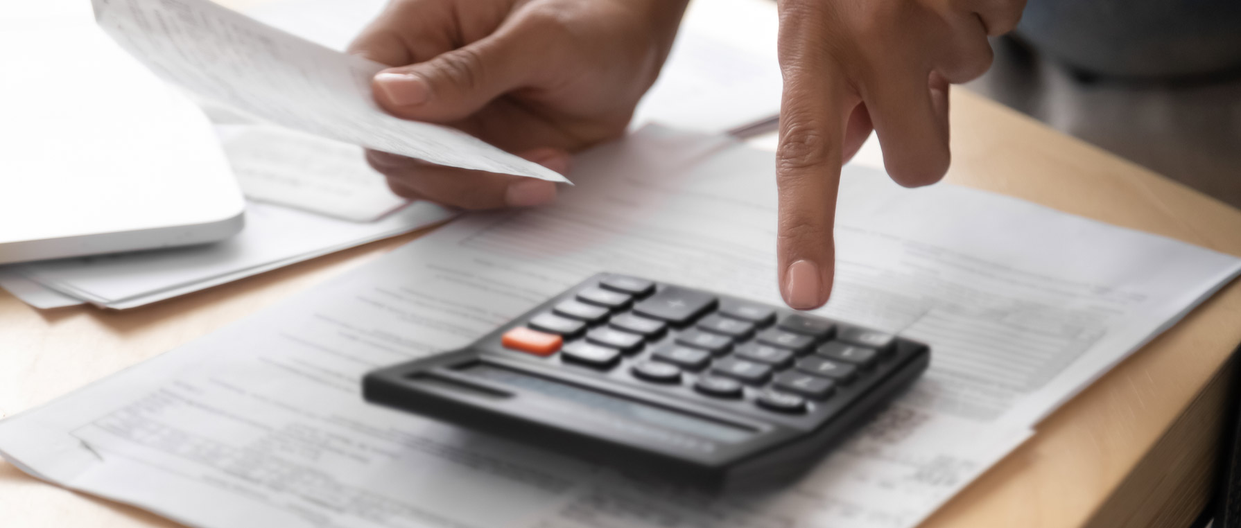 Hand using a calculator on table with papers