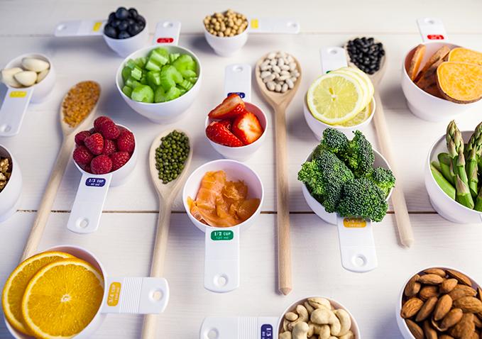 owoce i warzywa ułożone na drewnianych łyżkach i miskach