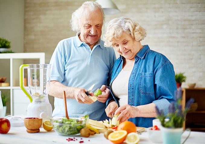 starsza kobieta i mężczyzna obierający owoce w kuchni