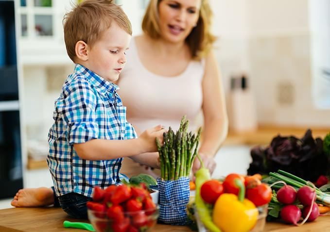 kobieta i dziecko dotykające szparagów