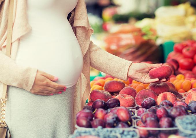 ciężarna kobieta trzymająca owoc na bazarze