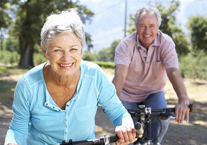 starsza kobieta i mężczyzna jadący na rowerach