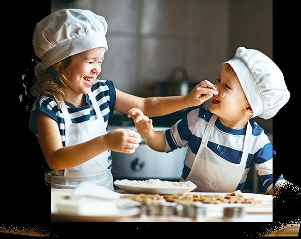 dwójka dzieci w fartuchach bawiąca się w kuchni