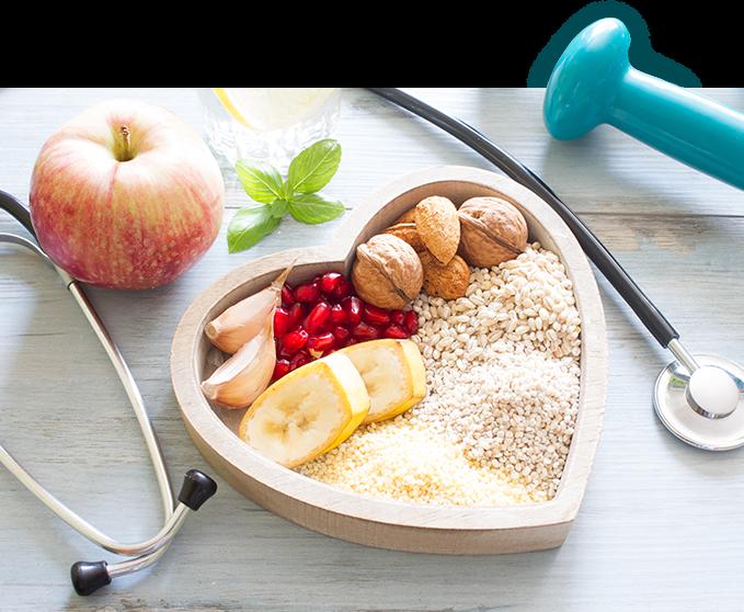 stolik na którym leży hantla, stetoskop, jabłko oraz miska w kształcie serca wypełniona owocami, ziarnami i warzywami