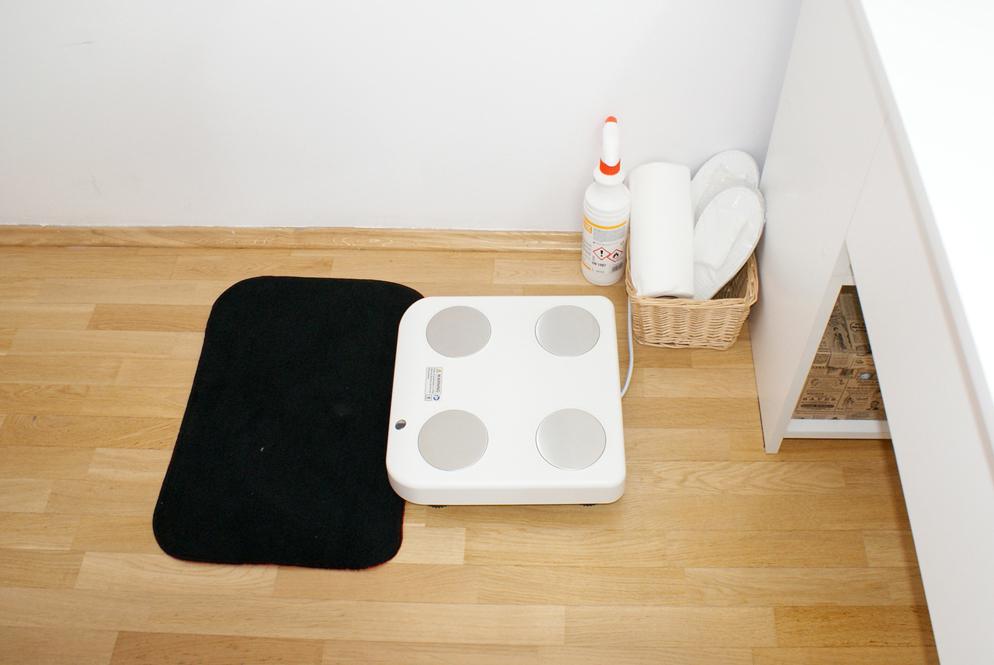 pokój z czerwonym fotelem i krzesłem, białym biurkiem na którym stoi czarna lampka oraz szafka z segregatorami