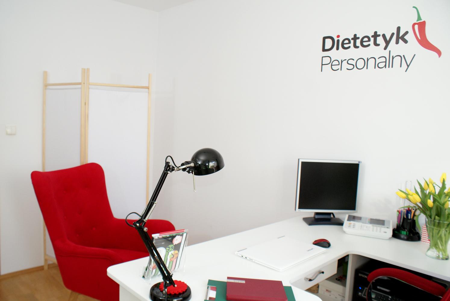 czerwony fotel za którym stoi analizator składu ciała tanita i parawan
