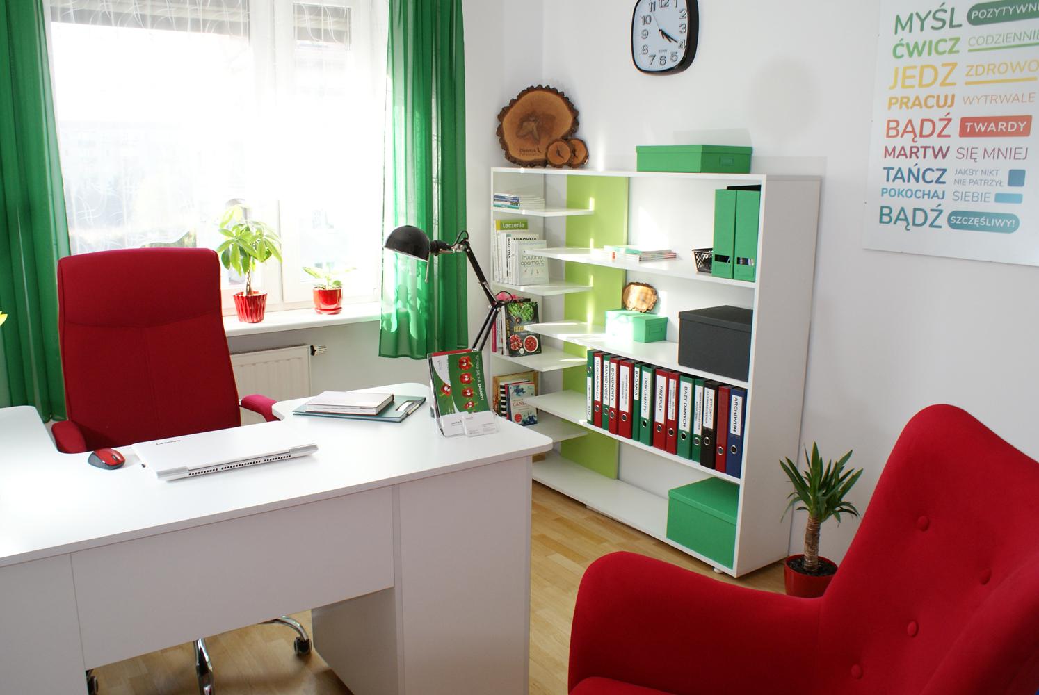 pokój z czerwonym krzesłem oraz białym biurkiem na którym stoi bukiet żółtych tulipanów