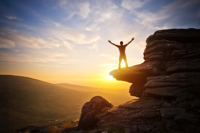 człowiek z uniesionymi rękami na szczycie góry