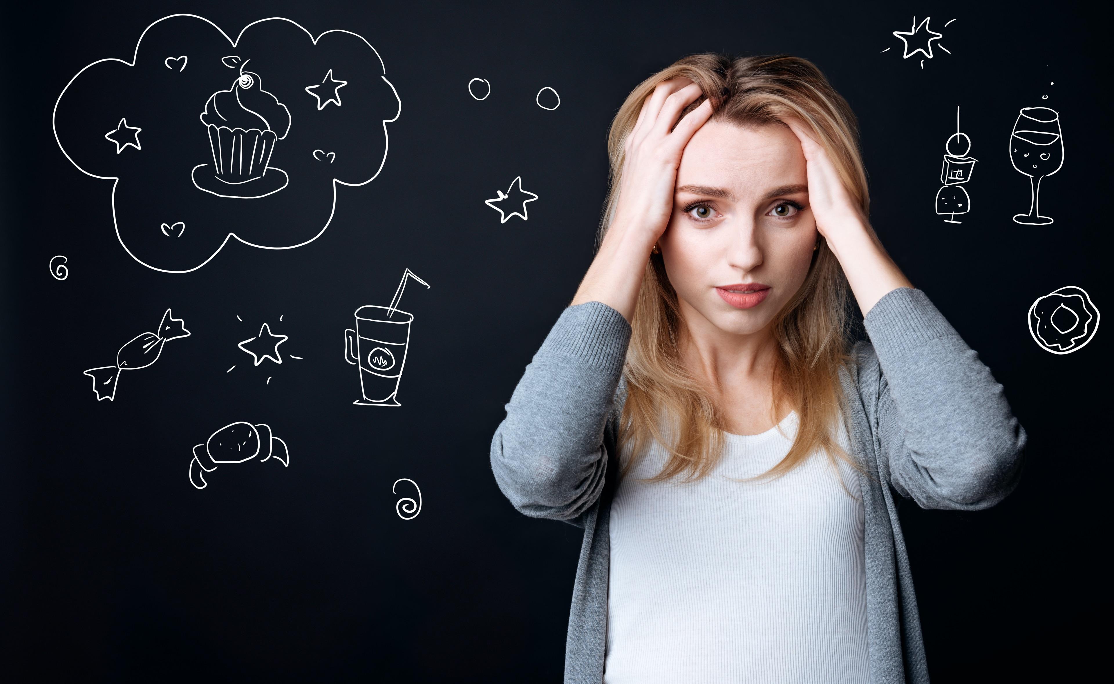 kobieta myśląca o jedzeniu i trzymająca się rękami za głowę