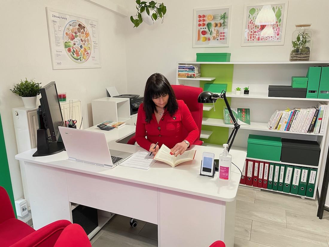 pokój z czerwonym fotelem i krzesłem oraz białym biurkiem na którym stoi czarna lampka
