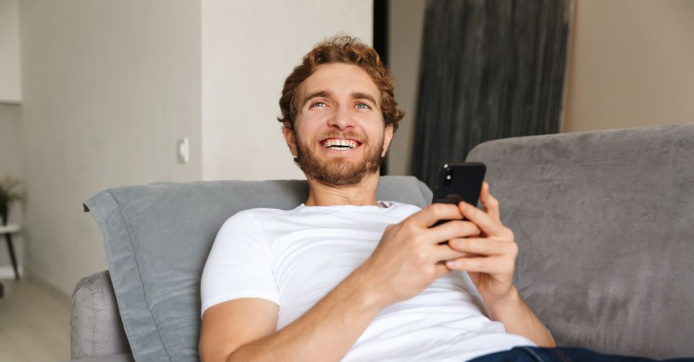 a young man on a sofa with a phone