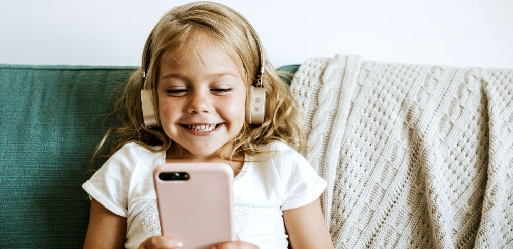A kid playing a game on her phone