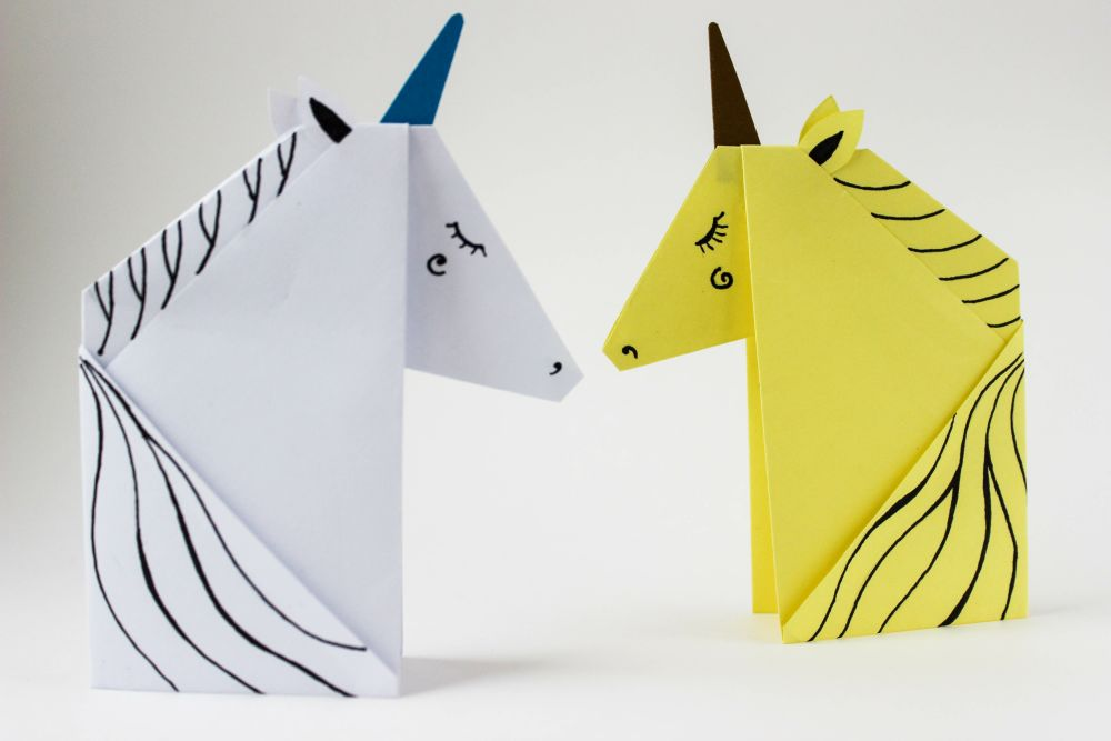 White and yellow unicorns made in the origami technique on white background